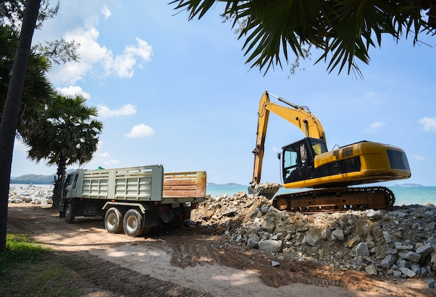 Graafwerktuiggraversteen en dump-vrachtwagen die op bouwwerf werken