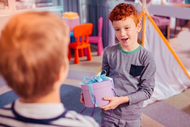 Graag gedaan. vrolijke jongen die een glimlach op zijn gezicht houdt en naar zijn vriend kijkt