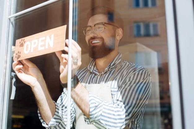 Graag gedaan. vrolijke opgetogen man die lacht terwijl hij het bord op het raam zet
