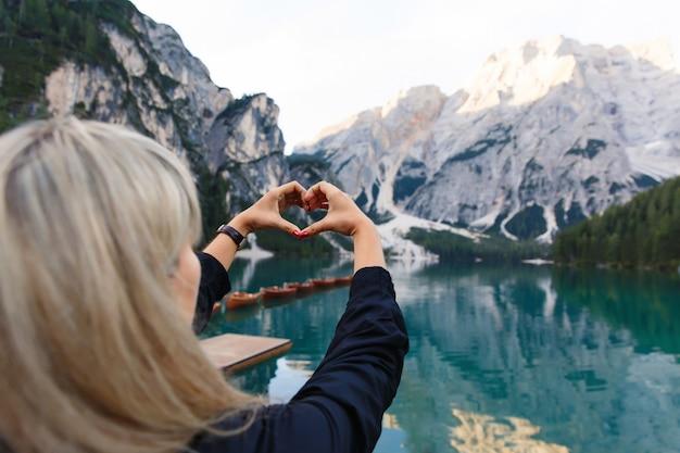Graag reizen en avontuur. vrouw wandelaar vertoont hart teken