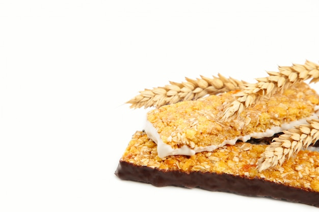 Graan energie granola bars en aartjes van tarwe geïsoleerd op wit. evenwichtig eiwitontbijt.