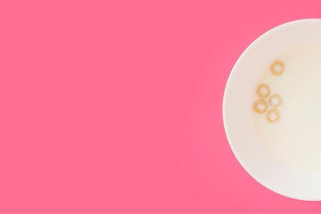 Graan granen ringen drijvend op de melk in de witte kom op roze achtergrond
