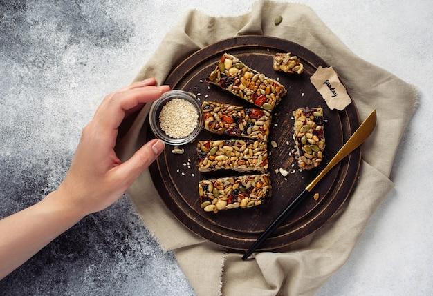 Graan mueslireep met noten, fruit en bessen op een witte stenen tafel