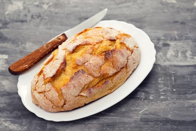 Graanbrood met mes op witte schotel