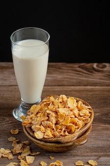 Graangewas in kom en melk op donkere houten achtergrond