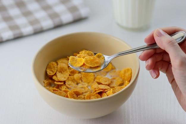 Graangewas met melk in een kom. de mens eet ontbijt.