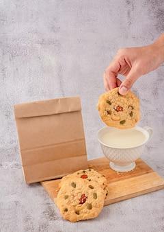 Graankoekjes, een kopje melk en een papieren zakverpakking worden op een snijplank geplaatst en met de hand nemen ze granenkoekjes en dompelen ze in de beker melk.