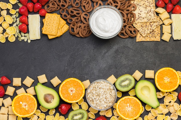 Graankoekjes sap, fruitjamkoekjes, aardbeien, kiwihoning, sinaasappelsap. zwarte achtergrond. ingrediënten voor het ontbijt.