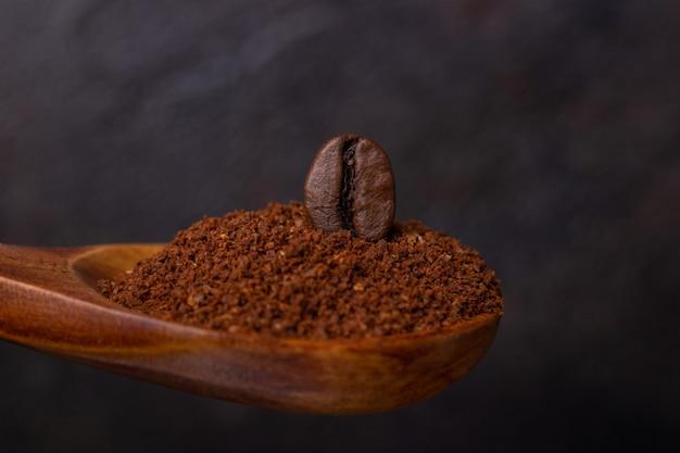 Graankoffie in een houten lepel van gemalen koffie op een donkere achtergrond
