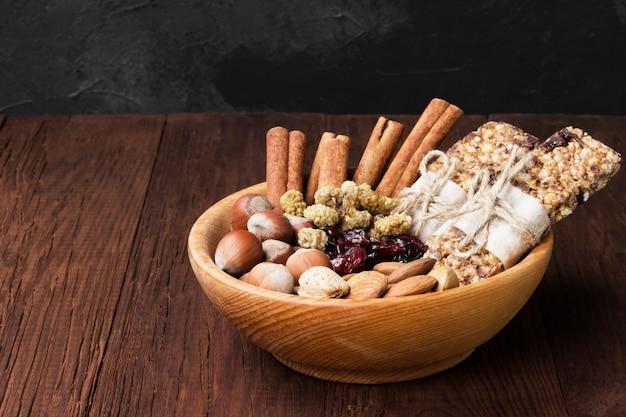 Graanrepen met noten, bessen en kaneel op een houten achtergrond