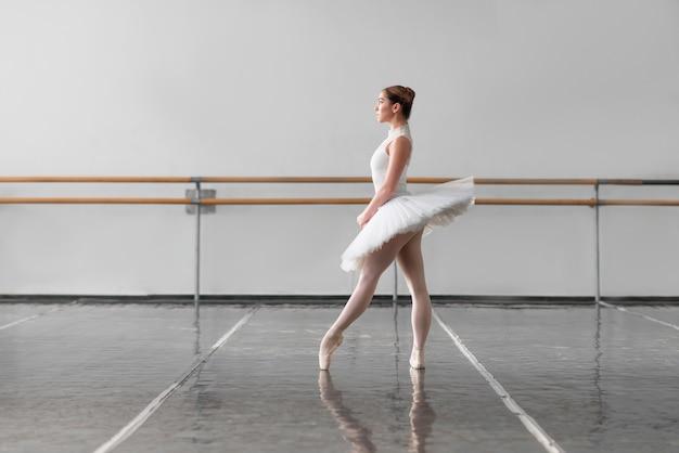 Grace ballerina houdt het rek in balletles