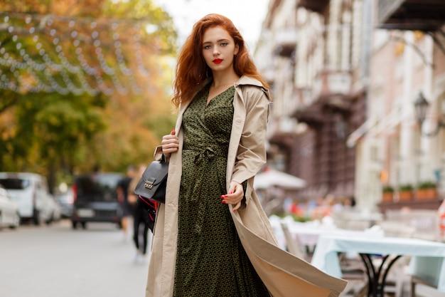 Gracieuze gembervrouw met golvende haren in beige jas. rode lippen en nagels.