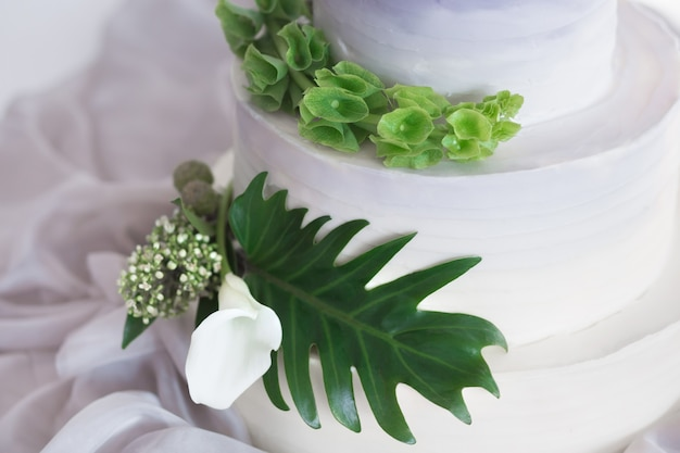 Gradiënt lila met witte multilevel bruidstaart met bloemen en groene palmbladeren