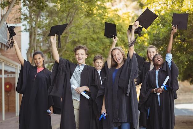 Graduate school kids staan met graad scroll en baret op de campus