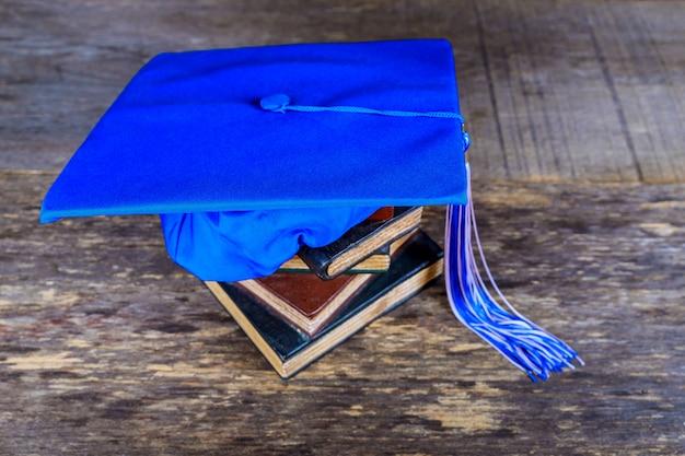 Graduatiebaret bovenop stapel boeken op abstracte achtergrond
