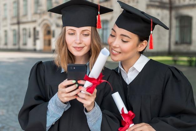 Graduatieconcept met studenten die smartphone bekijken