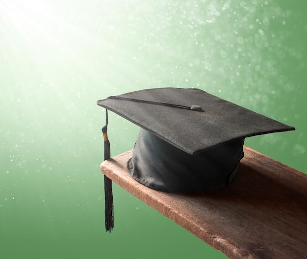 Graduatieglb, hoed op hout met abstrac groen achtergrondgraduatieconcept.