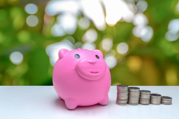 Graduatiehoed op spaarvarken met stapel van muntstukkengeld, besparingsgeld voor onderwijsconcept