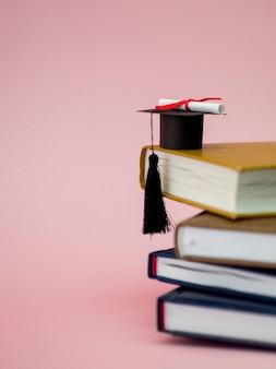 Graduation cap en diploma op verschillende boeken met kopie ruimte