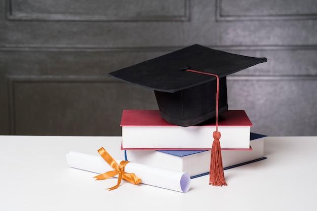 Graduation cap met boeken op wit bureau, onderwijs achtergrond