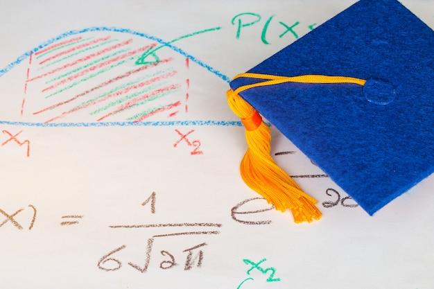 Graduation cap op papier wiskundige formule vergelijking op scherm klaslokaal