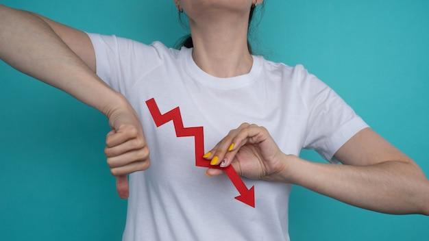 Grafiekdiagram groeit naar beneden in de hand. rode pijl omhoog in de hand van een vrouw op een blauwe achtergrond.