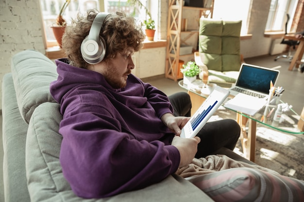 Grafieken controleren. man aan het werk vanuit huis, extern kantoorconcept. jonge freelancer, manager die taken doet met smartphone, laptop, tablet heeft online conferentie.