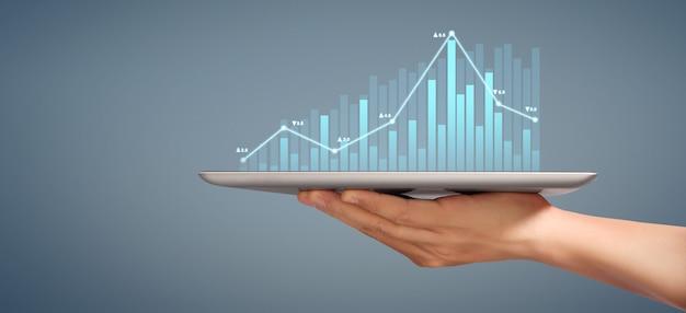 Grafiekgroei en toename van grafiekpositieve indicatoren in zijn bedrijf, tablet in de hand