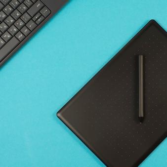 Grafiektablet en toetsenbord op een blauwe achtergrond.