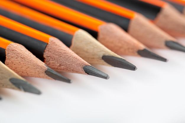 Grafietpotloden bekleed eenvoudig voor het schrijven en tekenen van dichterbij op wit bureau