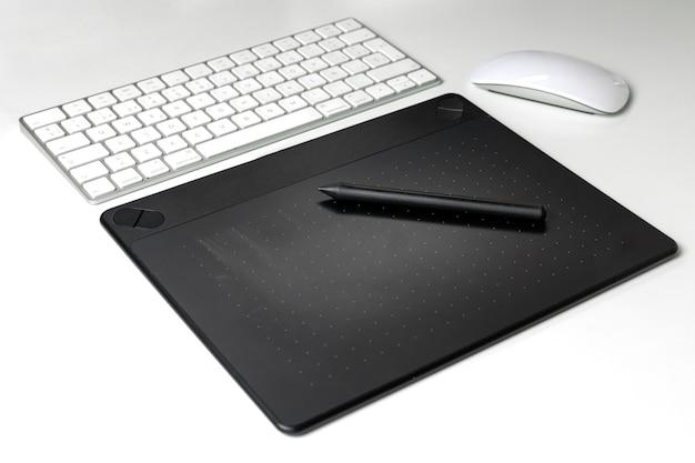 Grafisch digitizerpalet met toetsenbord en muis op witte bureauachtergrond