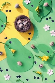 Grafisch kleurrijk ontwerp pasen achtergrond. plat lag, top uitzicht met kwarteleitjes, schaar, hart met tekst pasen, freesia bloemen.
