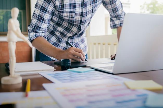 Grafisch ontwerp en kleurstalen en pennen op een bureau.