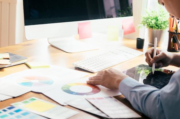 Grafisch ontwerper die aan computer en gebruikte grafische tablet werkt.