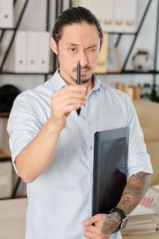 Grafisch ontwerper die één oog sluit en punt van digitale pen in zijn hand bekijkt