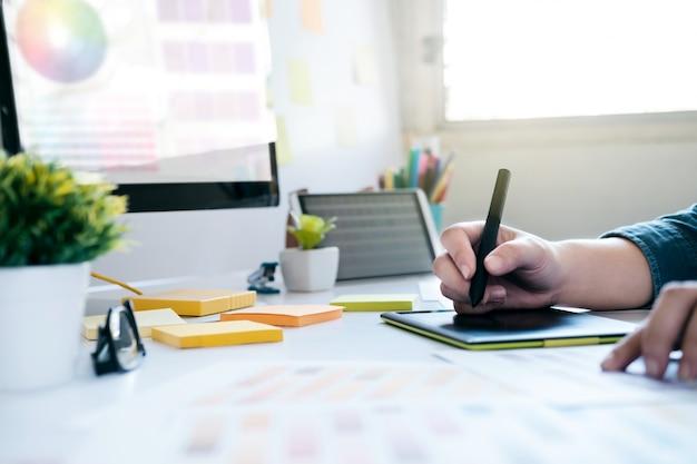 Grafisch ontwerper die grafiektablet gebruiken om het werk bij bureau te doen
