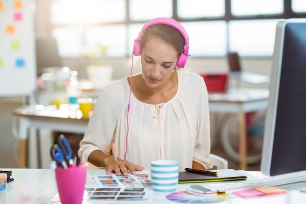 Grafisch ontwerper luisteren naar muziek en kijken naar kleurstaal