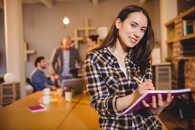 Grafisch ontwerper maakt aantekeningen in haar dagboek