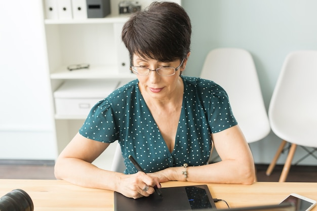 Grafisch ontwerper met behulp van haar tablet in een helder kantoor.