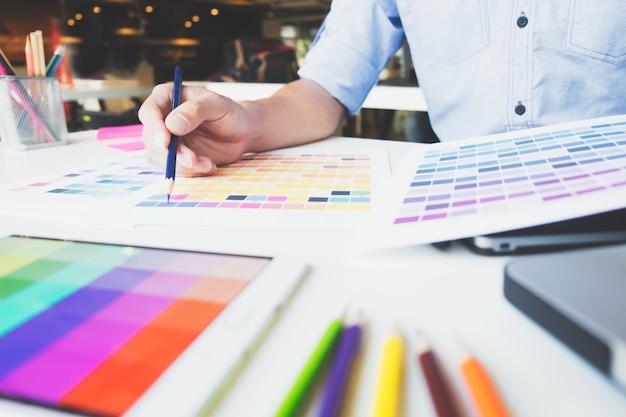 Grafisch ontwerper op het werk. kleurstaal monsters.