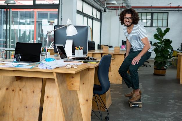 Grafisch ontwerper schaatsen met skateboard in creatief kantoor