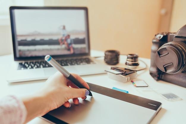 Grafisch ontwerper werkt met interactieve pendisplay, digitale tekentablet en pen op een computer. vloeiende tracking-opname met mooie lensflare met achtergrondverlichting.