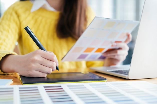 Grafisch ontwerper werkt met kleurstalen voor selectie.