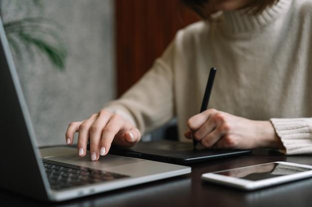 Grafisch ontwerper werkt vanuit huis, met behulp van laptop en digitale tekentablet om visuele concepten te creëren