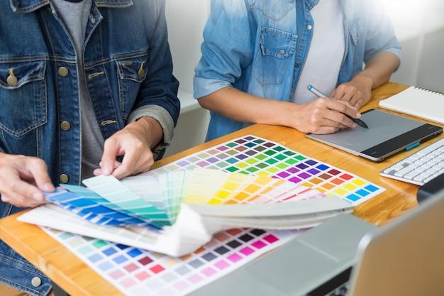 Grafisch ontwerpersteam die aan webontwerp werken die kleurenmonsters gebruiken die kunstwerk bewerken die tablet en een naald gebruiken bij bureaus in bezig creatief bureau.