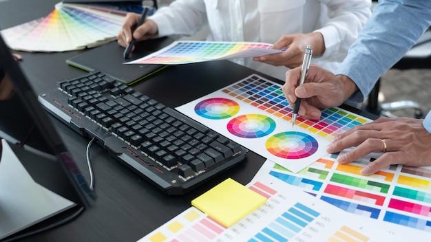 Grafisch ontwerpteam dat werkt aan webdesign met kleurstalen en illustraties bewerken met behulp van tablet en een stylus op bureaus in creatief kantoor.