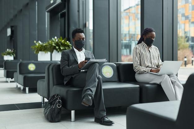 Grafisch portret over de volledige lengte van twee zakenmensen die maskers dragen terwijl ze in de wachtlounge op de luchthaven werken met sociale afstand, kopieer ruimte