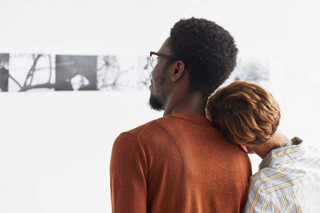 Grafisch portret van gemengd ras paar omhelzen tijdens het kijken naar schilderijen op moderne kunst galerie tentoonstelling,
