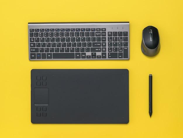 Grafisch tablet draadloos toetsenbord en muis op een gele tafel