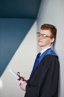 Grafisch verticaal portret van een jonge man die een afstudeerjurk draagt en een diploma vasthoudt terwijl hij naar de camera glimlacht op de universiteit